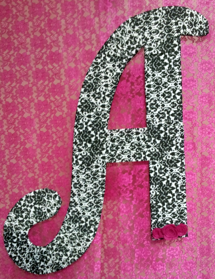 A custom monogram letter made of foam board and ribbon.
